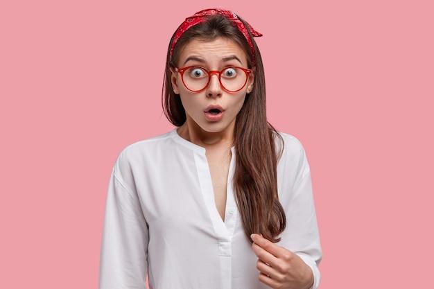 Foto na cabeça de uma jovem bonita e perplexa com uma expressão estupefata e olhando estupefata para a câmera, usando bandana e camisa branca