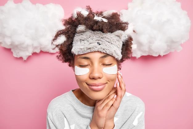 Foto na cabeça de uma jovem bonita tocando o rosto suavemente fecha os olhos sorri agradavelmente aplica adesivos de colágeno sob os olhos usa máscara de dormir pijama casual acorda de manhã