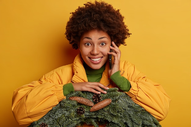 Foto na cabeça de uma jovem de pele escura conversando ao telefone, segurando um celular moderno perto da orelha, vestida com agasalhos de inverno, segurando uma coroa de flores verde