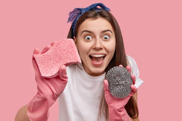Foto na cabeça de uma jovem feliz que olha com alegria, tem a boca aberta, mantém os germes longe, limpa a poeira com esponjas, usa luvas de borracha, bandana, termina as tarefas domésticas, posa sobre a parede rosa