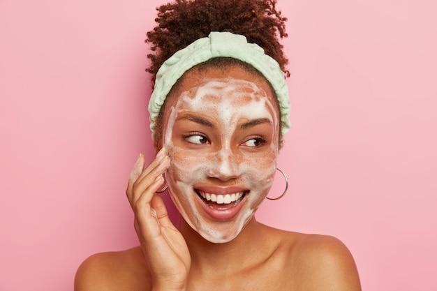 Foto na cabeça de uma jovem modelo bonita de pele escura tocando a bochecha com espuma, lavando o rosto com água e sabão, olhando alegremente para o lado, usa brincos redondos, bandana