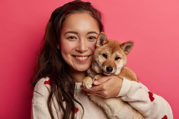 Foto na cabeça de uma jovem morena alegre adota um cachorrinho, abraça o cachorro com pedigree, sorri agradavelmente, se preocupa com o animal de estimação e usa um macacãozinho quente