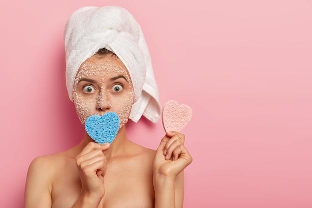 Foto na cabeça de uma jovem surpresa com olhos arregalados, usa uma toalha branca na cabeça molhada e segura duas esponjas em forma de coração