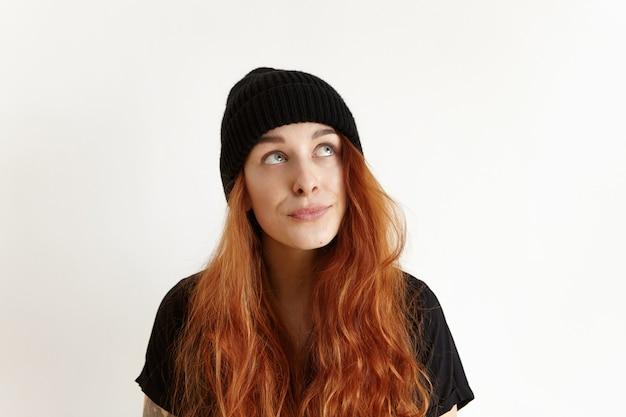 Foto na cabeça de uma linda adolescente caucasiana, duvidosa e indecisa com um penteado bagunçado