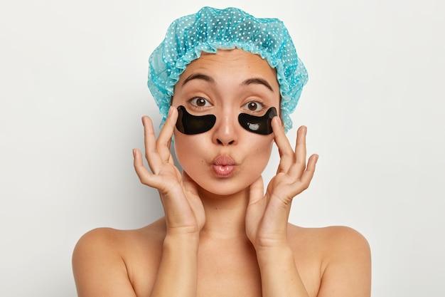 Foto na cabeça de uma mulher adorável usa touca de banho, aplica-se sob a máscara de tapa-olho para acalmar e renovar, mantém os lábios dobrados, reduz as linhas de expressão, fica com os ombros nus dentro de casa contra a parede branca