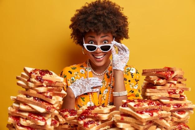Foto na cabeça de uma mulher afro-americana encaracolada positiva por baixo dos óculos de sol, vestida com roupas da moda e colar, passa o tempo livre visitando um café e come deliciosas torradas com geleia