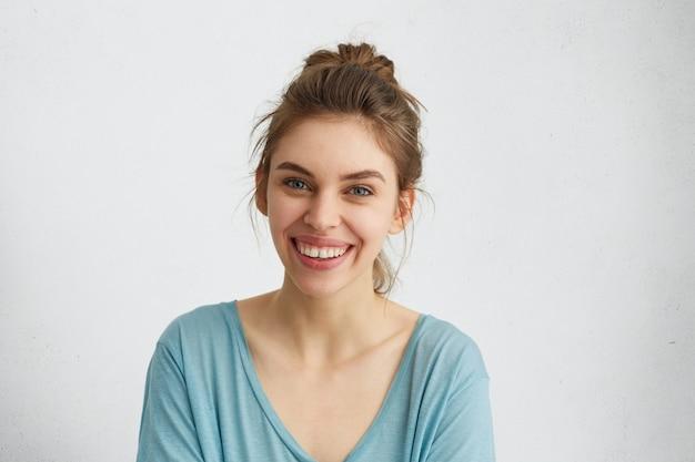 Foto na cabeça de uma mulher bonita com olhos azuis luminosos, rosto brilhante e sorriso gentil, regozijando-se com seu sucesso.