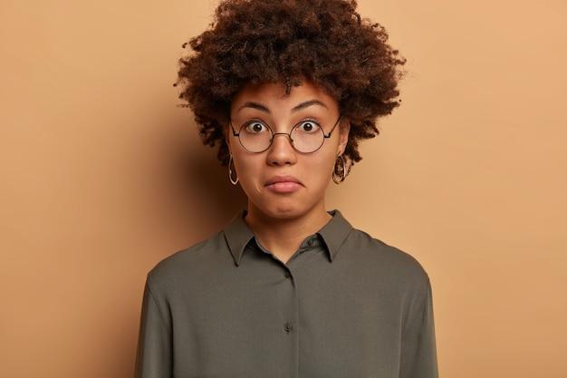 Foto na cabeça de uma mulher encaracolada com expressão maravilhada, expressa surpresa, ouve notícias intrigantes, usa óculos redondos