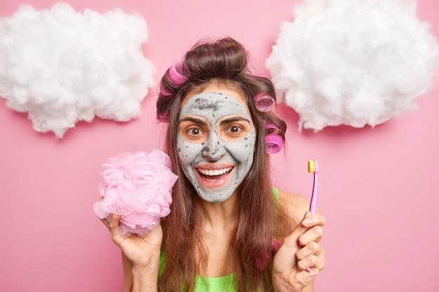 Foto na cabeça de uma mulher européia bonita positiva aplica máscara de argila nos rolos de cabelo do rosto segurando escova de dentes e esponja de banho tem rotinas matinais isoladas sobre parede rosa