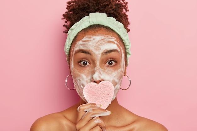 Foto na cabeça de uma mulher jovem e atraente com pele fresca e saudável, que faz procedimentos de higiene durante o fim de semana, usa bandana, cobre a boca com uma esponja cosmética, usa brincos redondos, parece com os olhos bem abertos