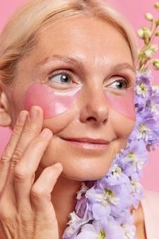 Foto na cabeça de uma mulher loira de meia-idade satisfeita colocando adesivos de hidrogel embaixo dos olhos