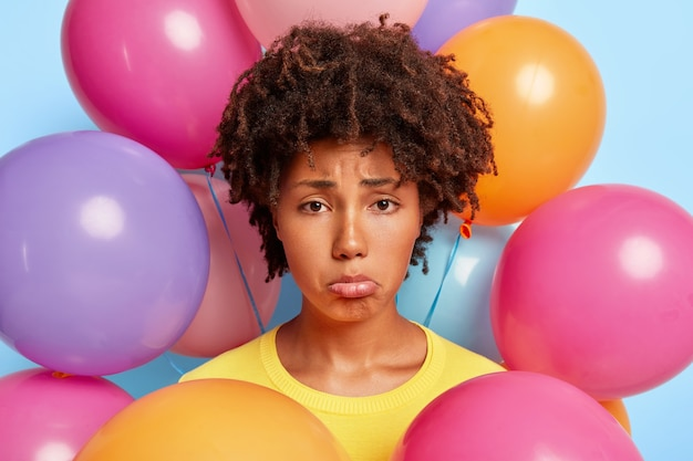 Foto na cabeça de uma mulher negra desesperada e triste que franze o lábio inferior, estando de mau humor durante a festa, sem amigos quer comemorar em grande companhia seu aniversário faz foto perto de balões coloridos feriado estragado