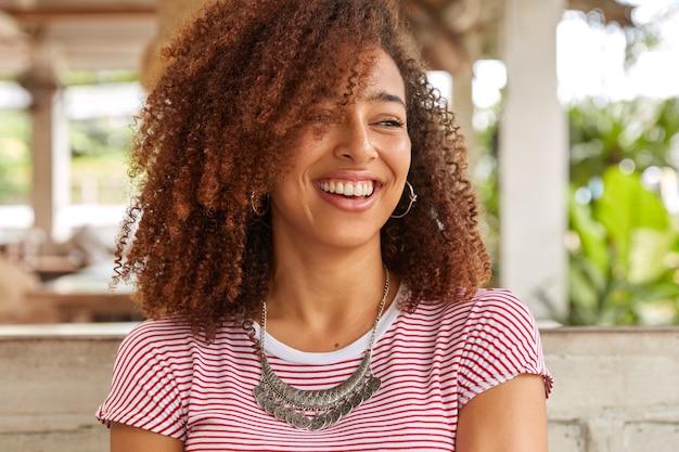 Foto na cabeça de uma mulher negra engraçada com cabelo encaracolado, ri de uma boa piada, tem um sorriso cheio de dentes, mostra dentes brancos perfeitos, usa uma camiseta listrada casual, posa na lanchonete do terraço