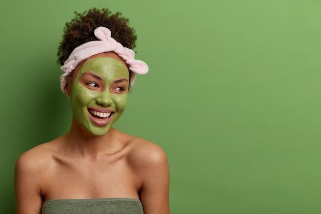 Foto na cabeça de uma mulher sorridente e despreocupada com os ombros nus, desvia o olhar com prazer, faz uma rotina facial de beleza para a pele, usa máscara verde no rosto, bandana, isolada na parede com espaço em branco