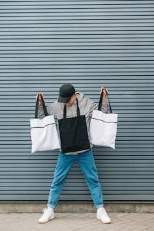 Foto na moda de um jovem em streetwear com sacos de eco nas mãos.