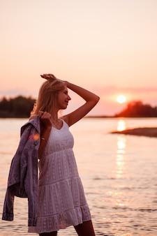 Foto no perfil de uma jovem loira linda e feliz em um vestido de verão branco fica no ...