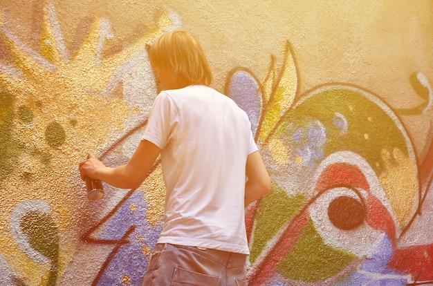 Foto no processo de desenhar um padrão de grafite em um velho muro de concreto