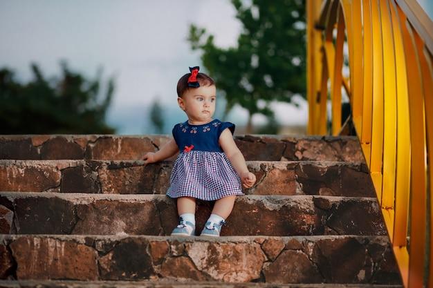 Foto noturna de um adorável bebê de nove meses sentado na escada olhando a treliça do jardim