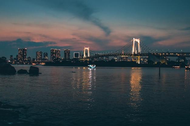 Foto panorâmica da cidade durante o amanhecer com vista para a ponte do arco-íris, cidade de minato, japão