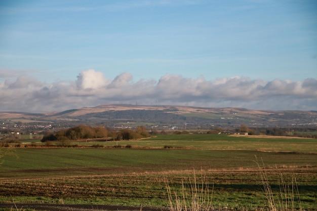 Foto panorâmica de campos verdes e colinas sob um céu azul nublado