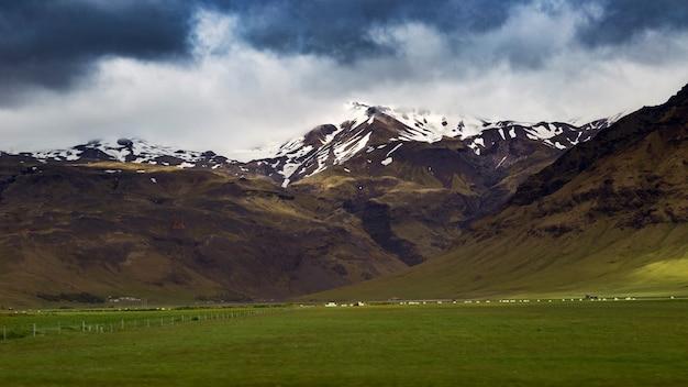 Foto panorâmica de colinas cobertas de neve sob um céu azul nublado em frente a um campo
