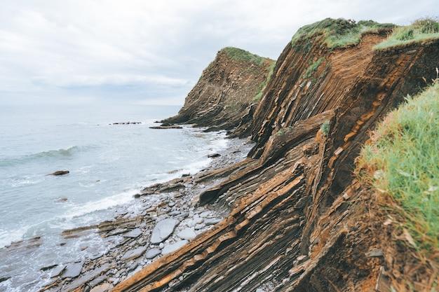 Foto panorâmica de penhascos cheios de grama verde ao lado do mar azul durante o dia