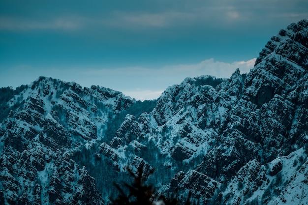 Foto panorâmica de picos de montanhas recortados cobertos de neve sob céu azul nublado