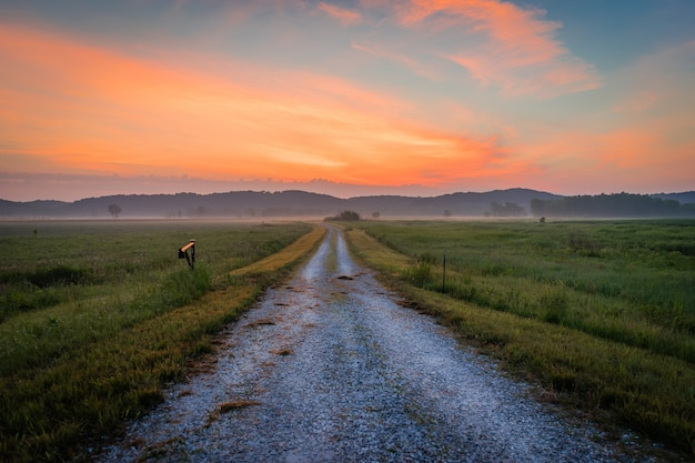 Foto panorâmica de um caminho de terra no meio de um campo com a silhueta das montanhas ao entardecer