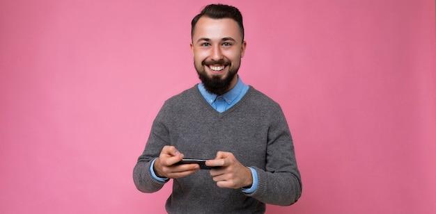 Foto panorâmica de um jovem moreno bonito com a barba por fazer e barba vestindo um suéter cinza