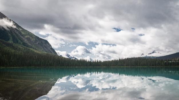Foto panorâmica de um lago alpino puro cercado por uma floresta