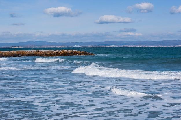 Foto panorâmica de um oceano com ondas e doca de pedra sob céu nublado