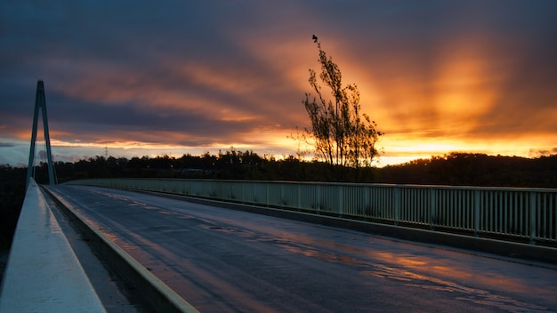Foto panorâmica de um pôr do sol em uma ponte com lindos raios irradiando do sol