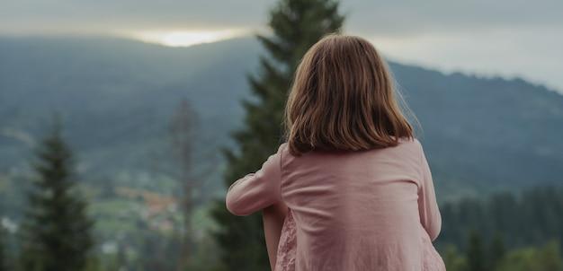 Foto panorâmica de uma menina assistindo o pôr do sol nas montanhas na ucrânia