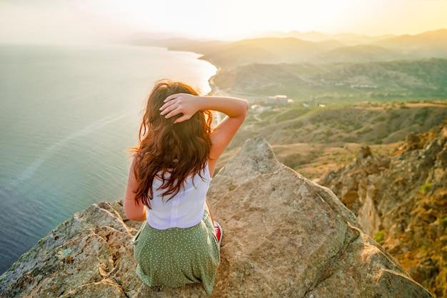 Foto panorâmica de uma mulher feliz que conquistou o topo de uma falésia com uma linda vista para o mar