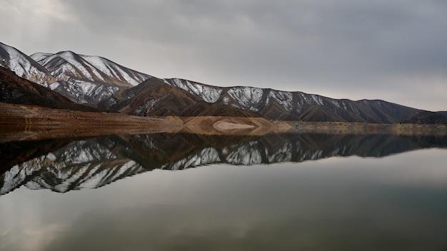 Foto panorâmica horizontal de uma cadeia de montanhas refletida nas águas do reservatório de azat, na armênia