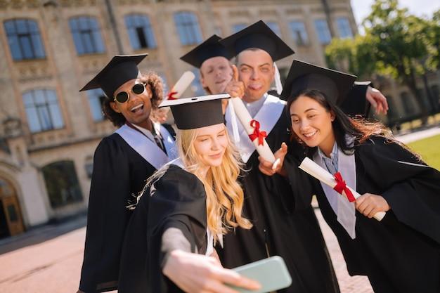 Foto para memória. linda garota tirando fotos com seus colegas de grupo após a formatura no pátio da universidade.
