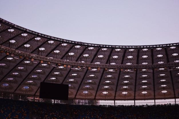 Foto parcial de um estádio exibindo o teto, um monitor grande com fileiras e cadeiras