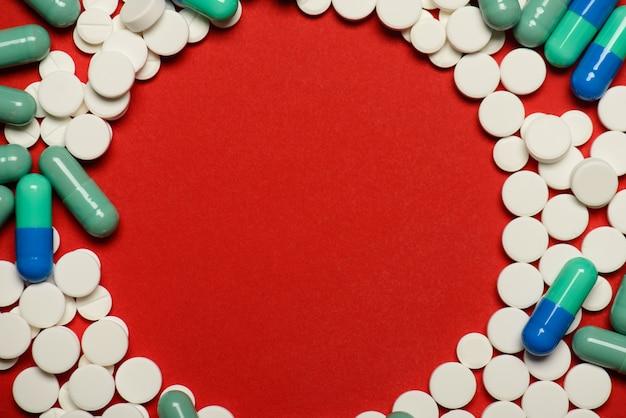 Foto plana de cima acima da cabeça de muitos lotes de pílulas e um lugar vazio no centro