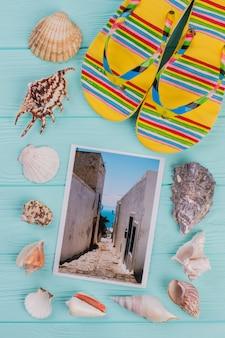 Foto plana leiga de uma rua estreita com conchas do mar e chinelos em torno dela fundo de madeira azul.