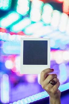 Foto polaroid no fundo de lâmpadas brilhantes