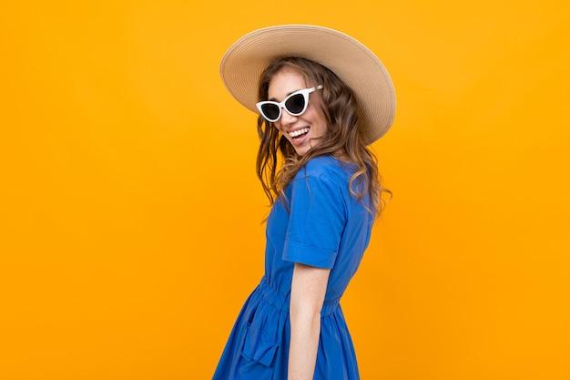 Foto por trás de uma garota em um vestido azul em uma mulher amarela e elegante de chapéu e óculos