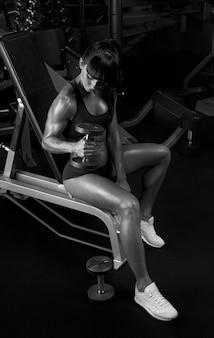 Foto preto e branco de mulher levantando halteres sentado no ginásio