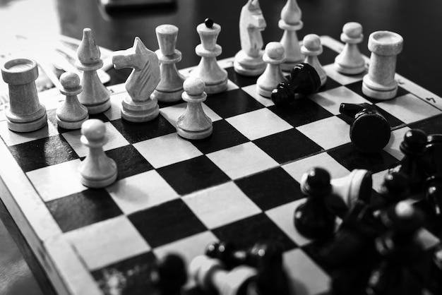 Foto preto e branco de peças de xadrez definidas no tabuleiro de xadrez na mesa. jogo de lazer