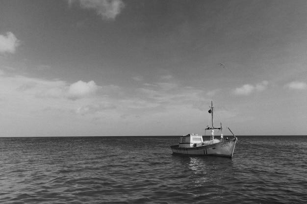 Foto preto e branco de um grande barco flutuando no mar aberto