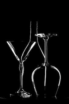 Foto preto e branco de uma garrafa de vinho e dois copos contra a parede preta