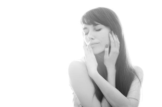 Foto preto e branco de uma menina em um fundo branco em uma pose suave