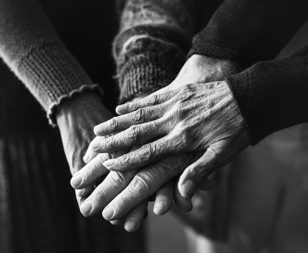 Foto preto e branco do close de mãos de pessoas sênior