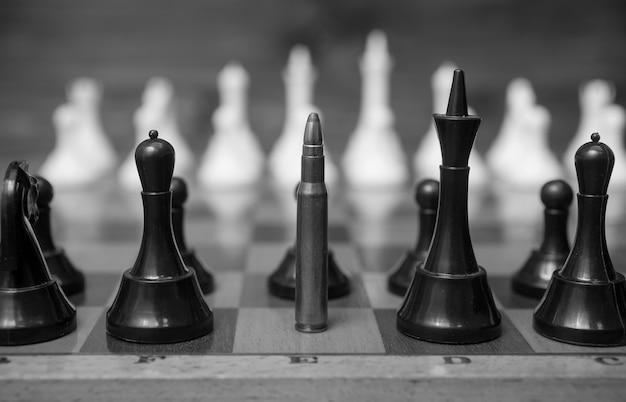 Foto preto e branco do close up de uma bala em uma fileira de peças de xadrez. foto conceitual do poder das armas.