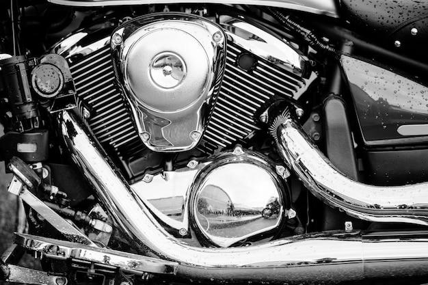 Foto preto e branco do close up do motor da motocicleta com muitos detalhes do cromo. motocicleta de estrada poderoso desempenho moderno com tubos de escape. motor chopper.