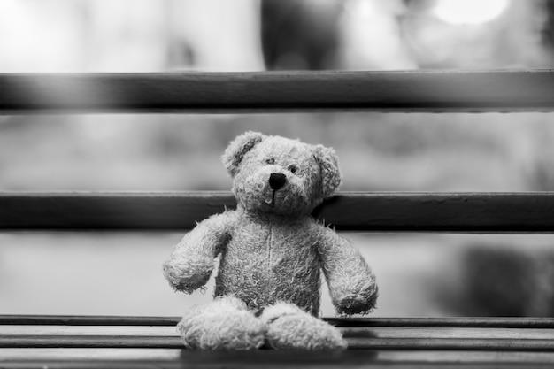 Foto preto e branco do urso de peluche com a cara triste que senta-se no beance de madeira, urso de peluche só que senta-se apenas fora no dia sombrio, conceito só, dia internacional das crianças faltantes.